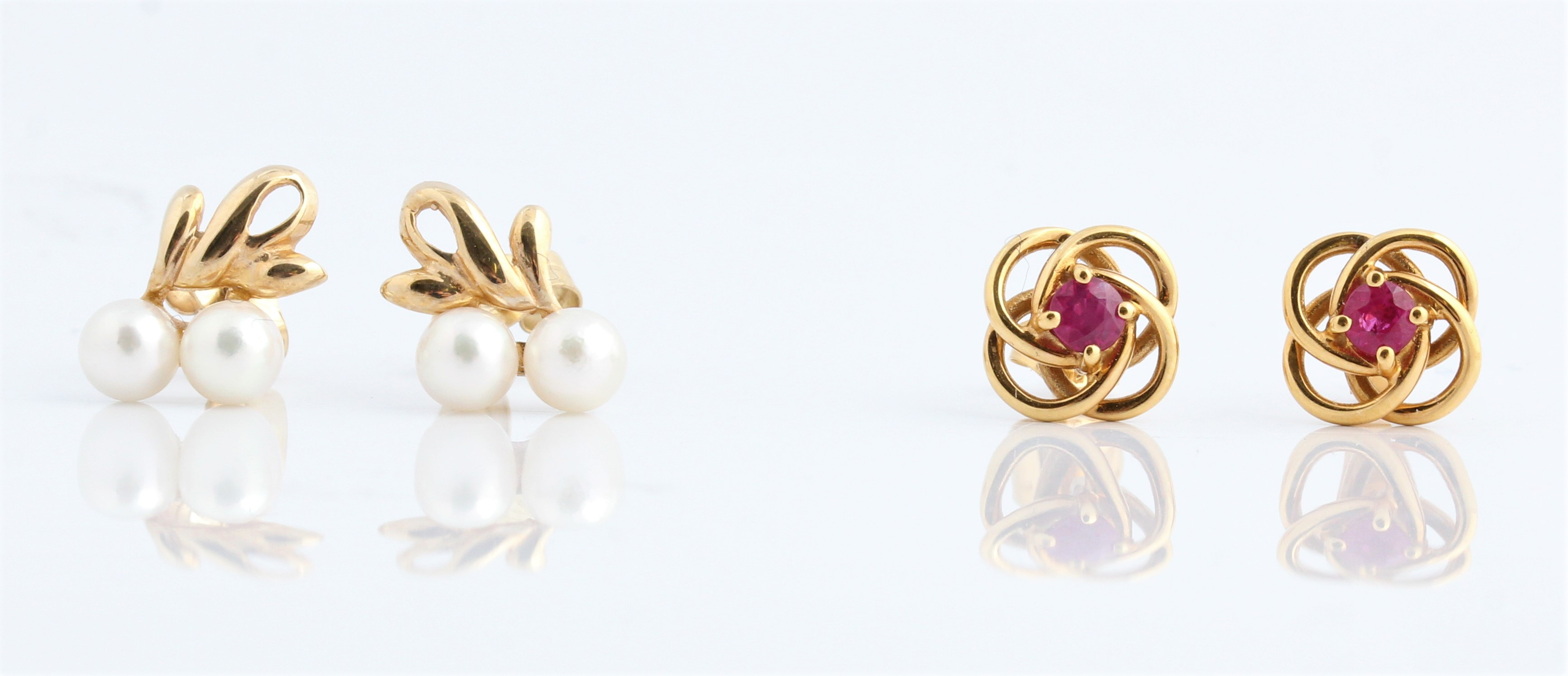 A pair of ruby set knot stud earrings, stamped 375, together with a pair of hallmarked 9ct yellow