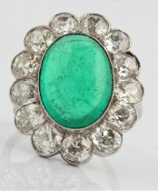An emerald and diamond cluster ring, set with a central oval emerald cabochon, measuring approx.