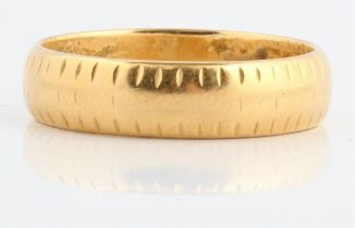 A hallmarked 18ct yellow gold patterned wedding band.