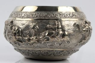 A Burmese white metal bowl, featuring repousse lion hunt scenes and floral design borders, stamped