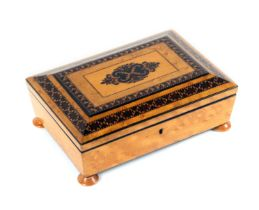 A small birds eye maple Tunbridge ware sewing box, of sarcophagal form and raised on four bun