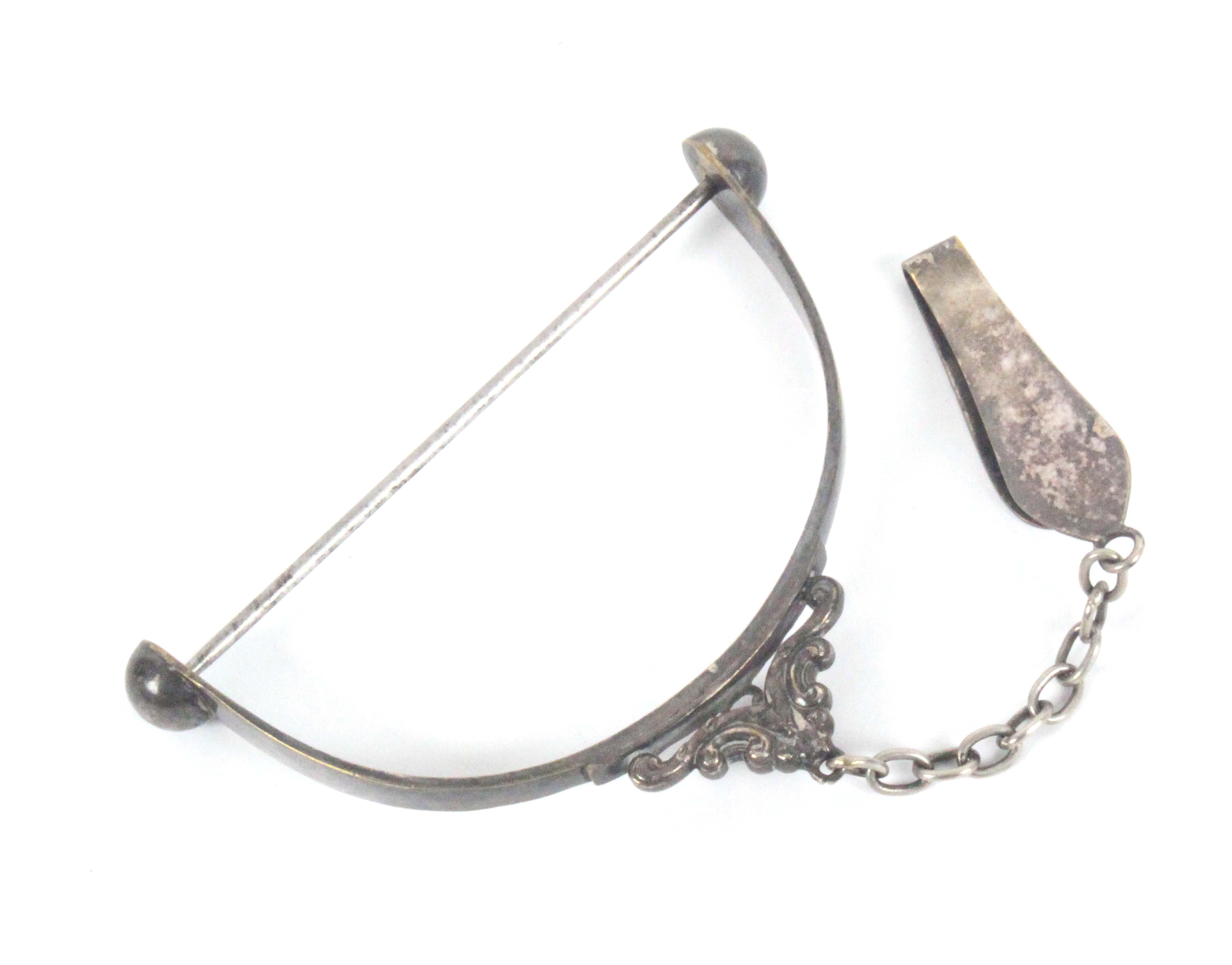 A silver plated spool knave, the stirrup form frame to a scroll mount, chain and chatelaine style