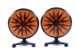A pair of rosewood miniature circular tilt top tables, each with a tri-form base and three bun
