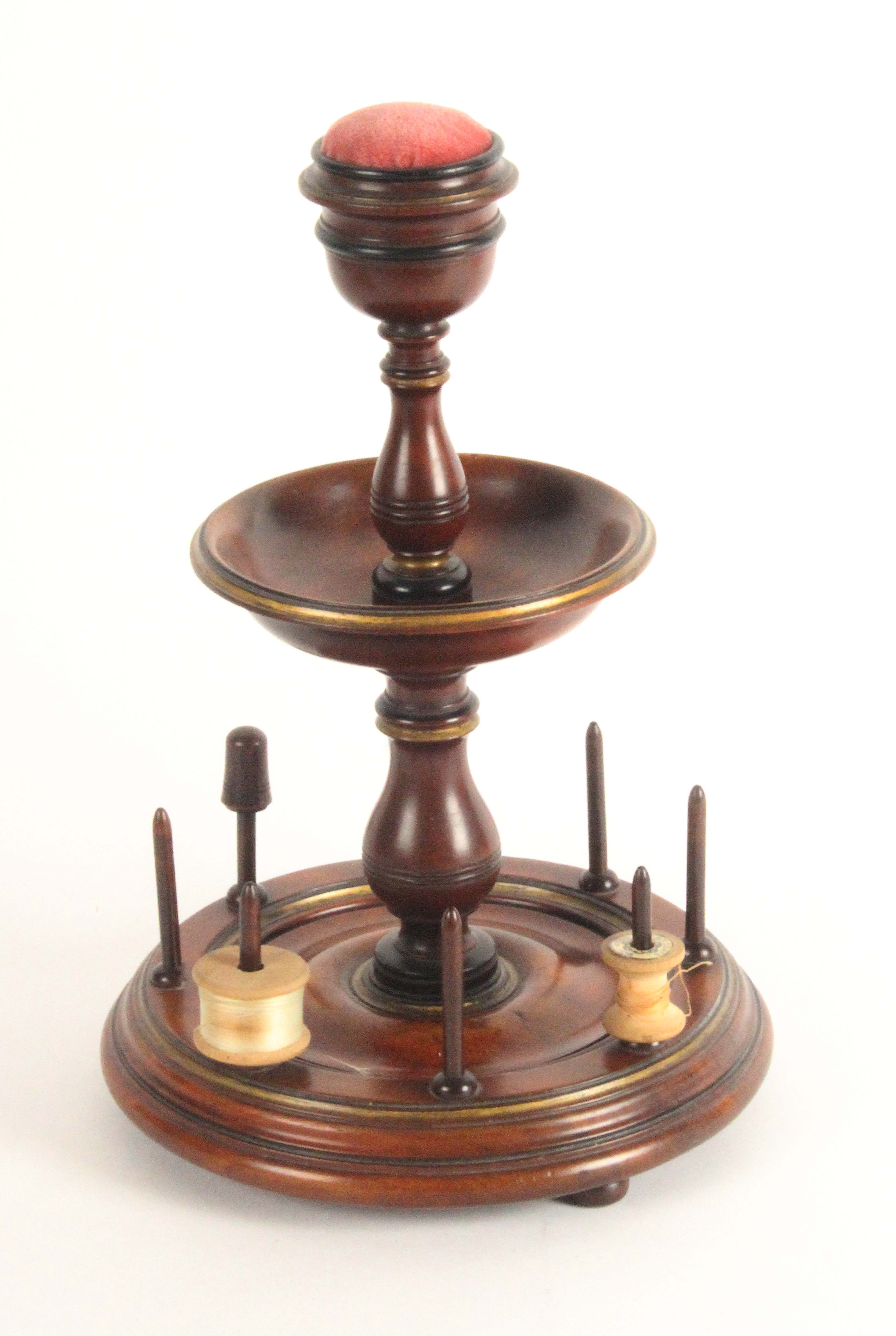 A mahogany reel stand, circa 1840, the turned circular base on three bun feet with seven reel spikes