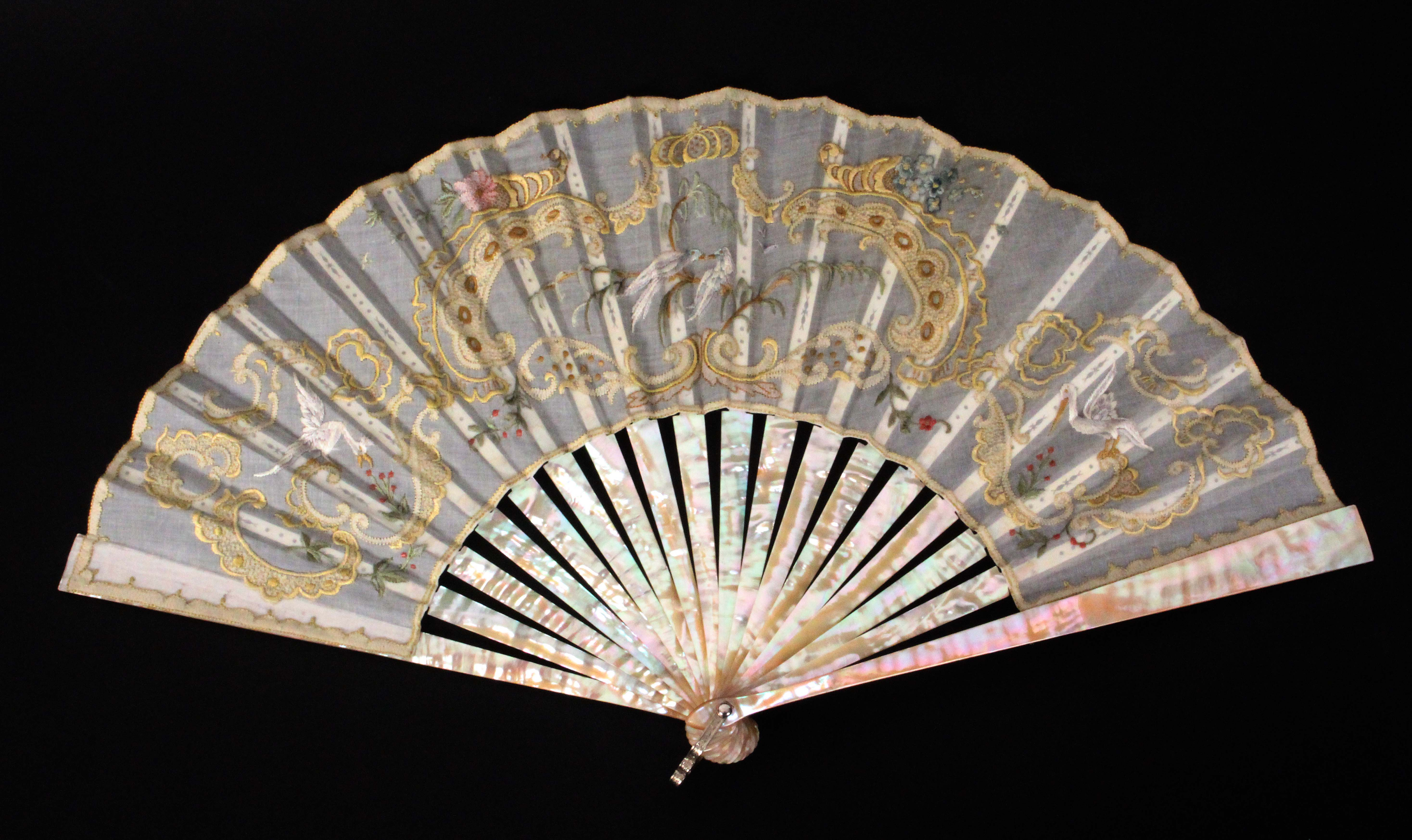 A 20th Century fan, mother of pearl guards and sticks, the fan embroidered with birds, flowers and