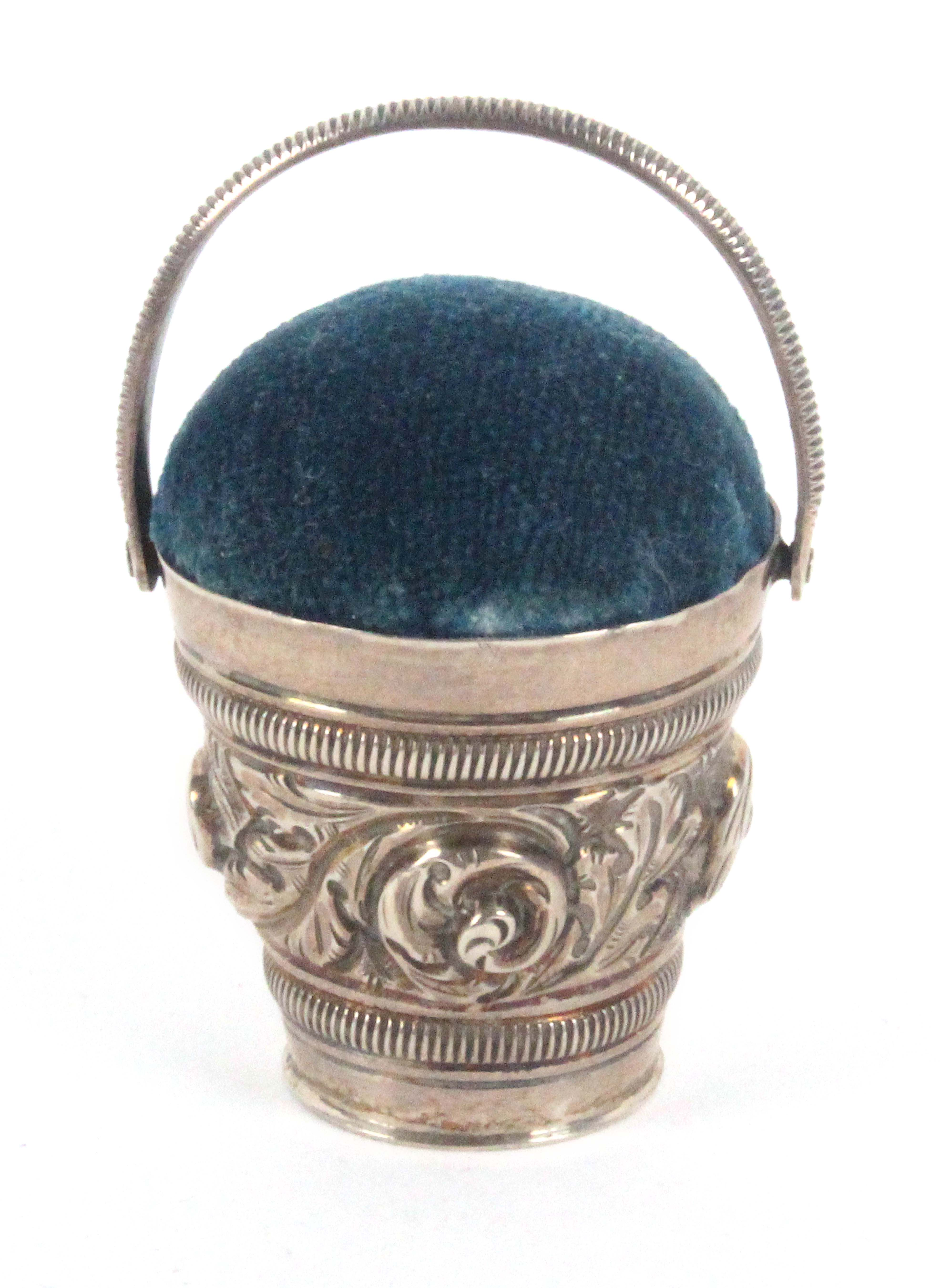 A silver bucket form pin cushion, decorated with a band of leaf scrolls, swing handle, 4.5cms.