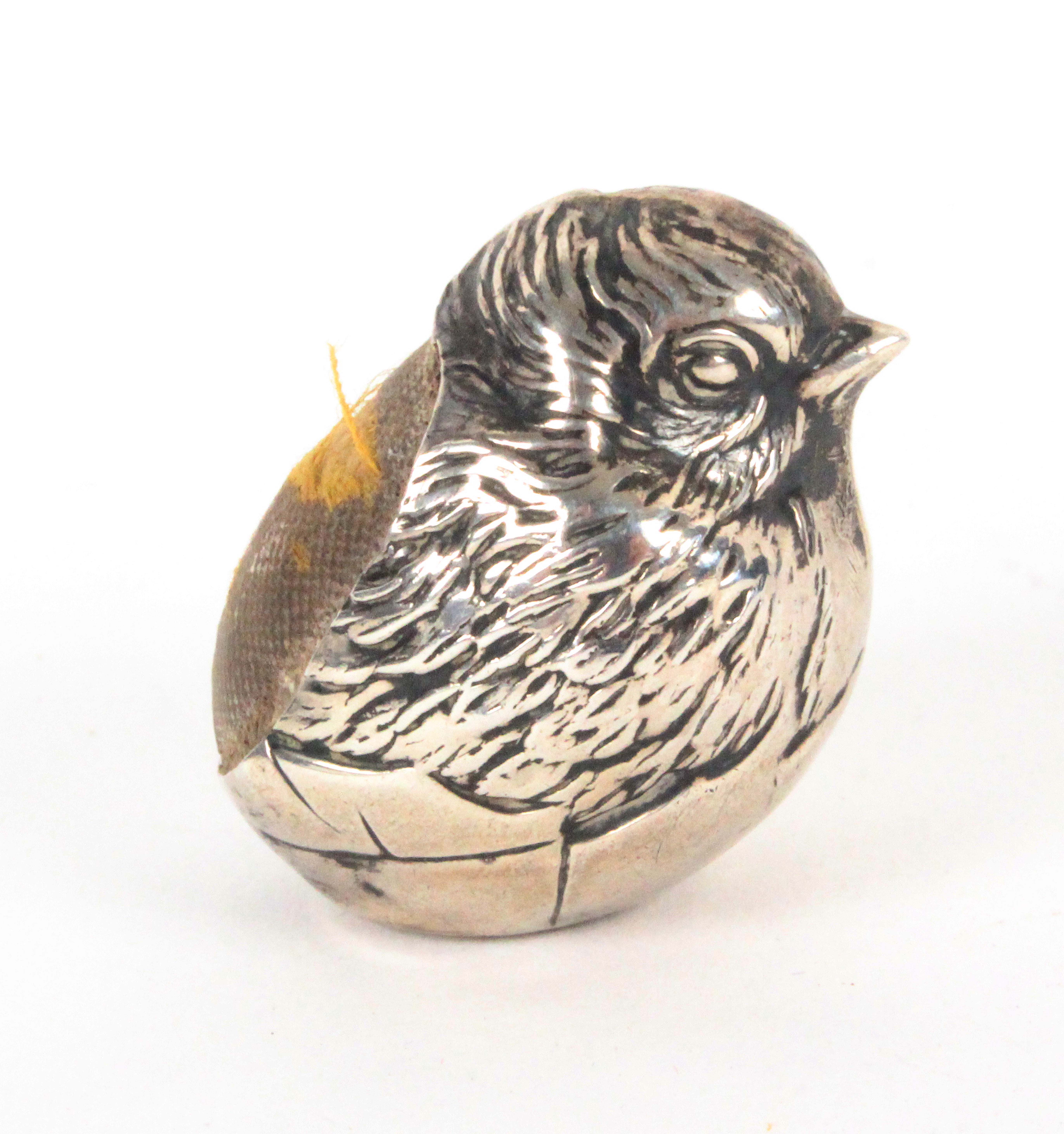 A small silver pin cushion in the form of a chick, emerging from its egg, Chester, 1908, by