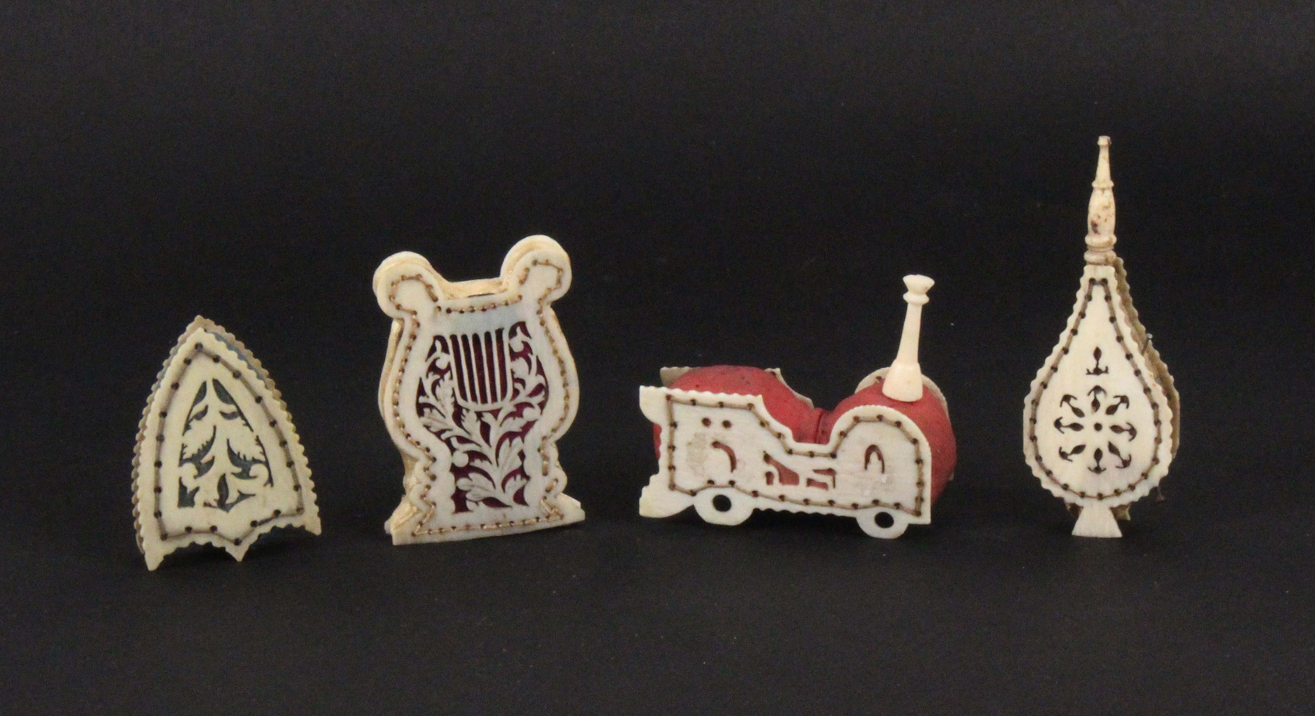 Four cut and pierced bone pin cushions, comprising an example as a railway locomotive, 5cms, another