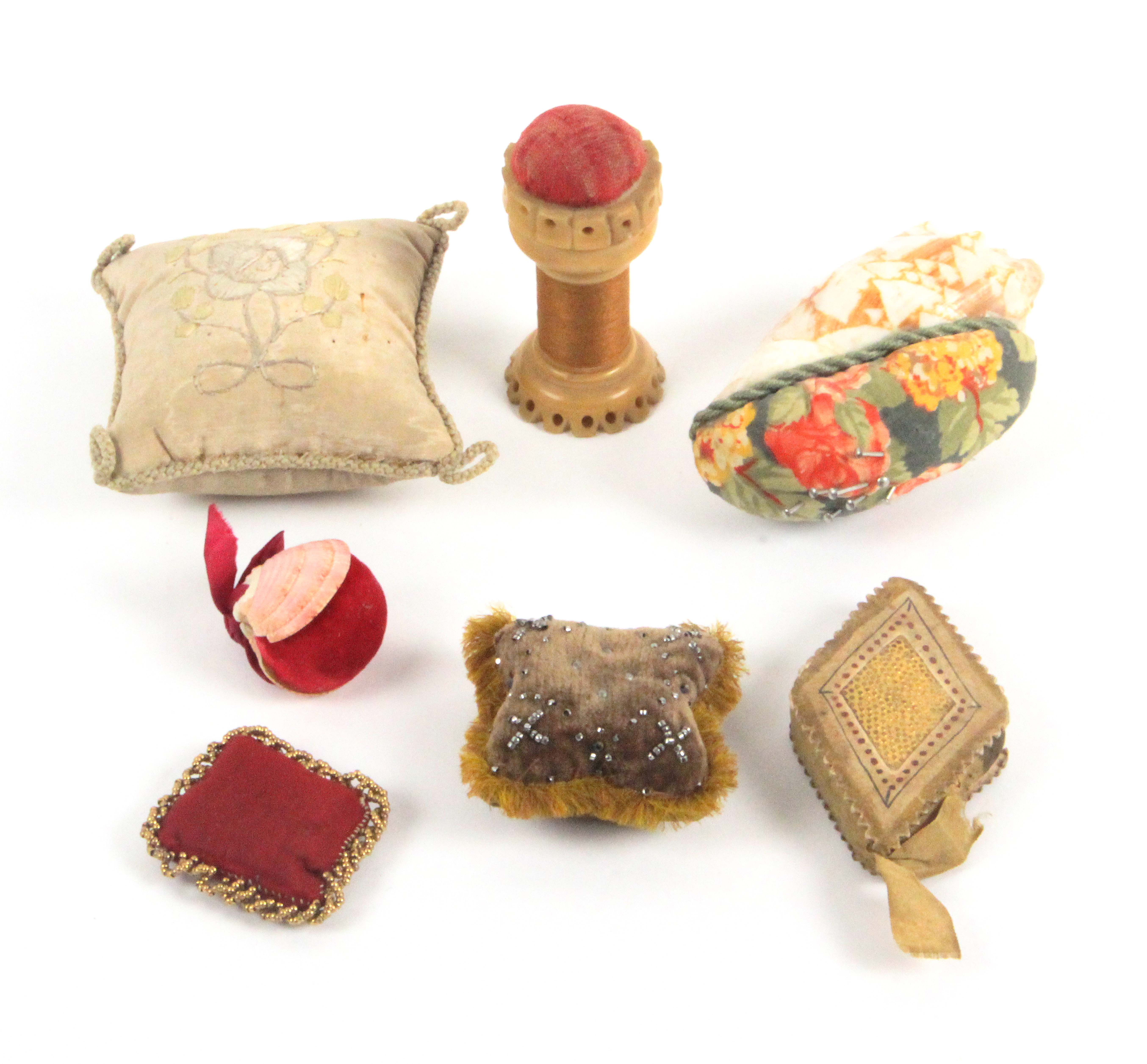 Seven pin cushions, comprising two formed from sea shells, largest 8cms, three cushion form material