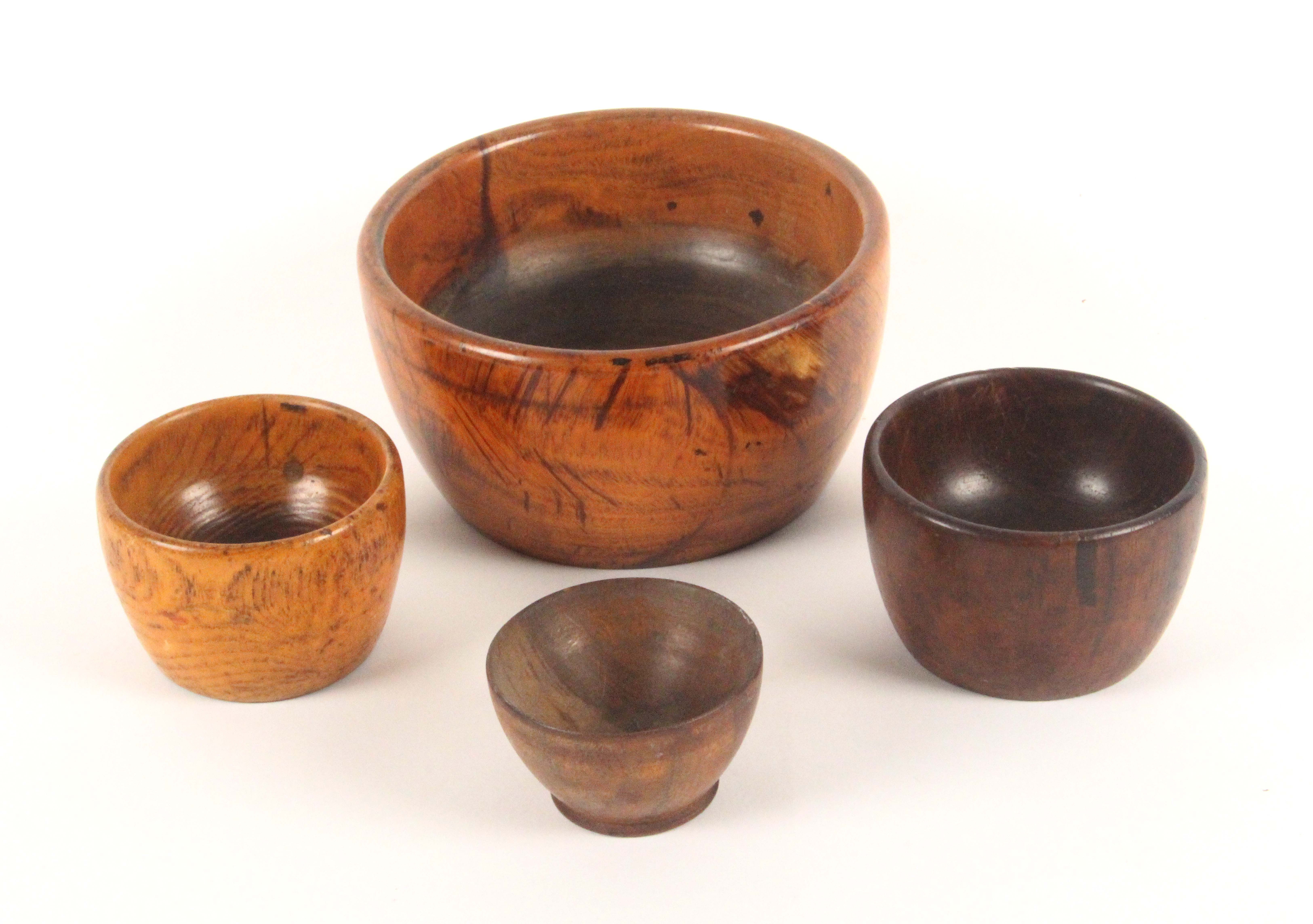 Four 19th Century wooden wool ball bowls, comprising a large lignum vitae example, 13cms, and