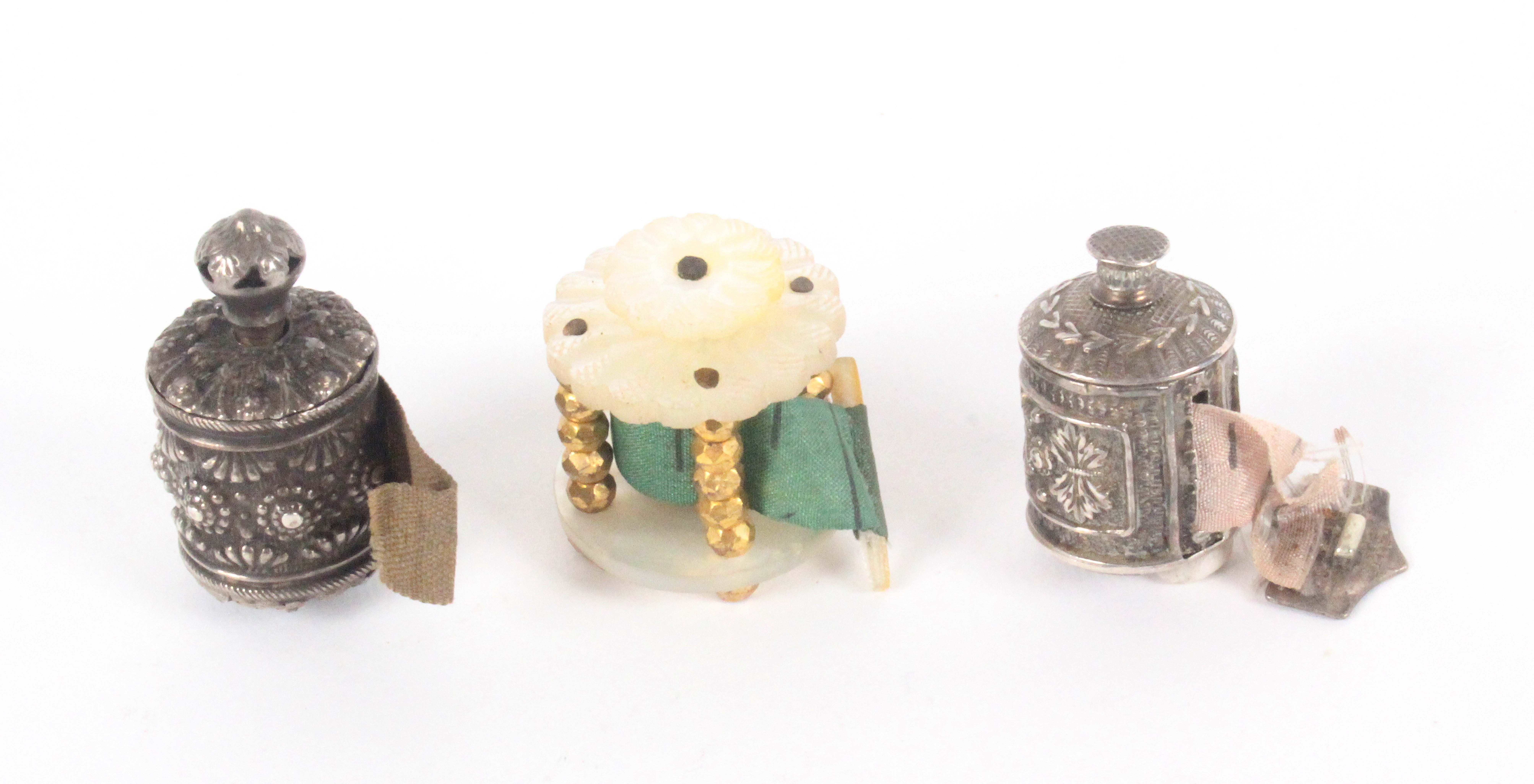 Three tape measures, comprising a silver cylinder example decorated with flower heads, reduced