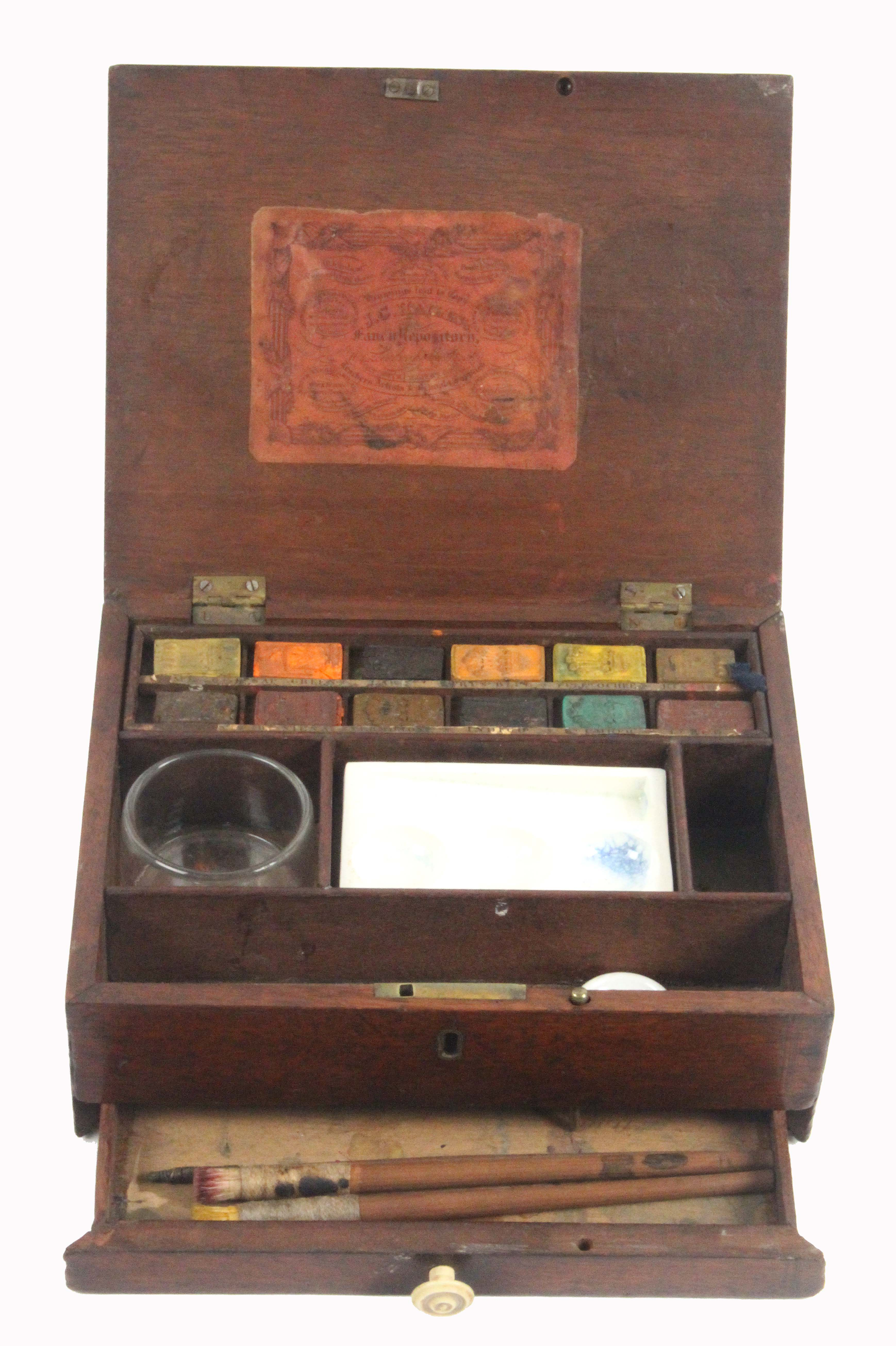 An early 19th Century mahogany paint box, of rectangular form, the lid interior with fancy printed