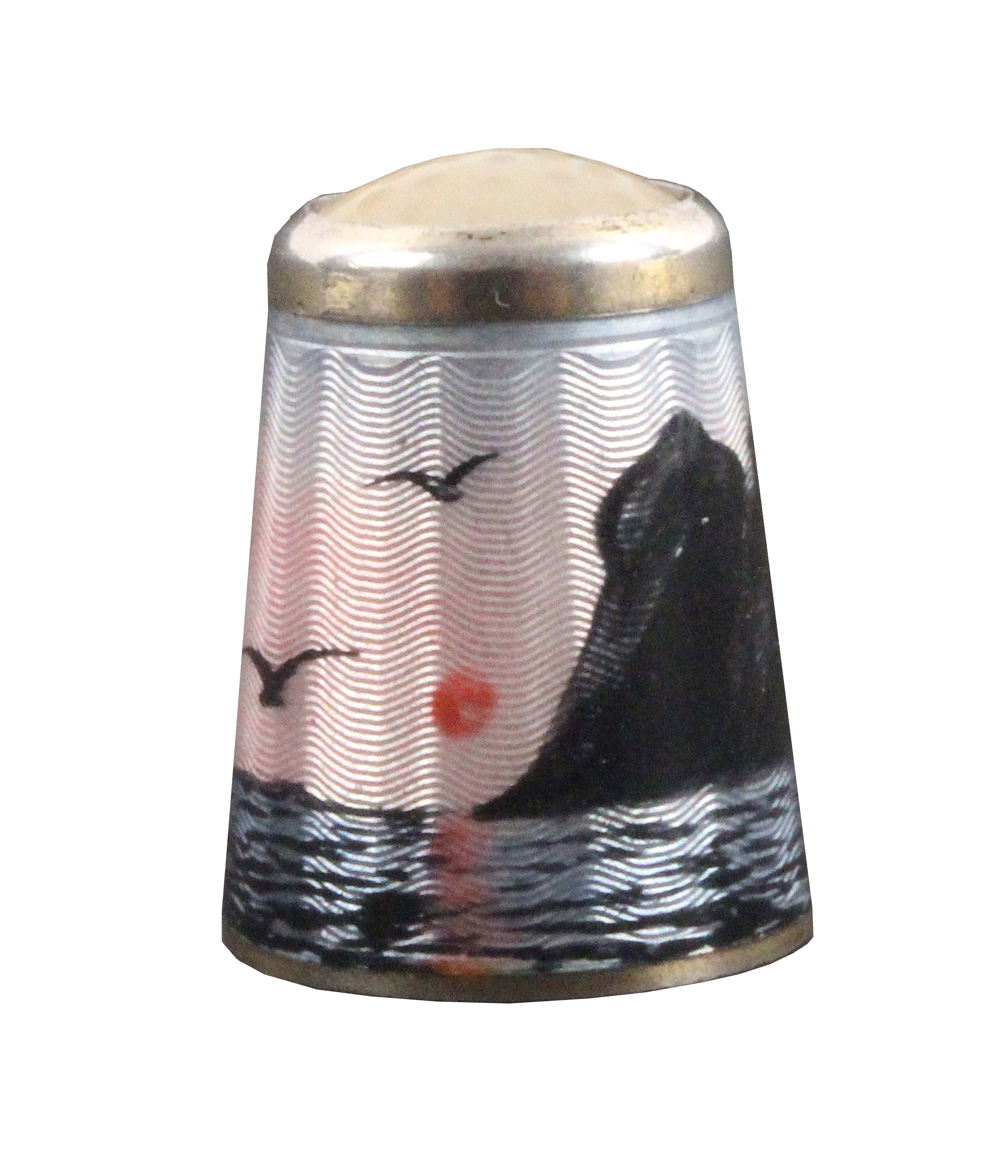 A Norwegian silver and enamel thimble, depicting North Cape with birds in flight over waves below