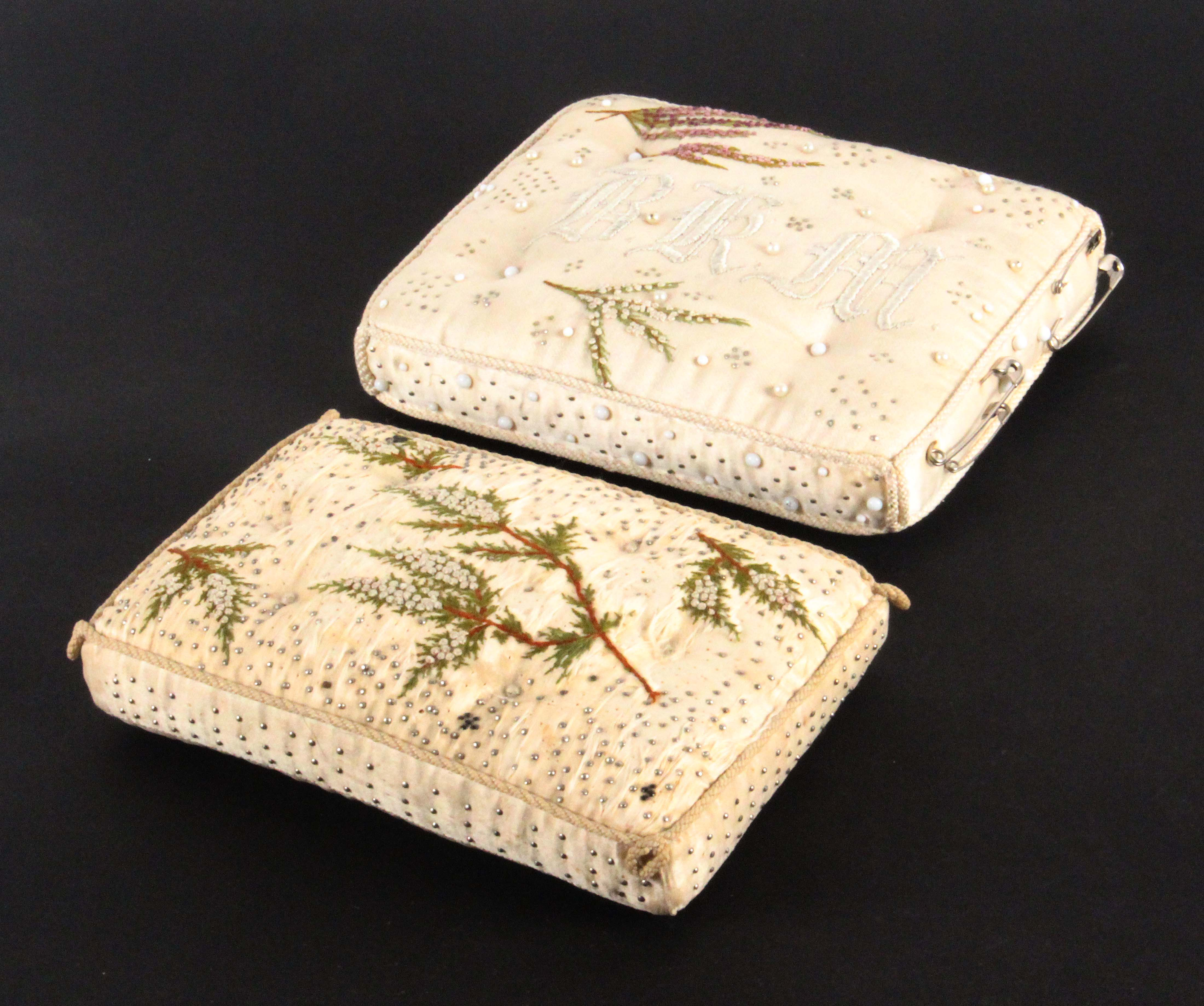 Two late 19th Century layette and embroidered pin cushions, comprising a rectangular example