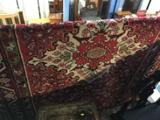 A Hamadan rug, the large floral medallion in pinks and ivory and having a triple guard stripe. 300cm