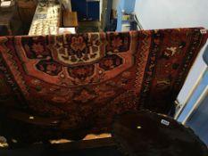 A Hamadan rug, the pink ground with midnight blue flower head medallion. 207cm x 132cm