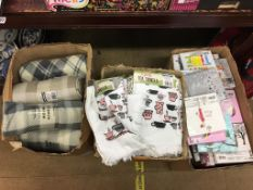Three boxes of as new throws, tea towels etc.