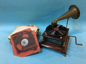 A wind up table top gramophone and various records