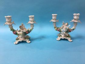 A pair of Continental candelabras, decorated with cherubs