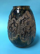 A glazed Oriental vase decorated with impressed lettering