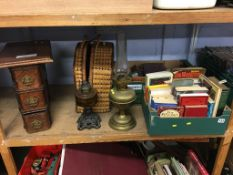 A shelf of assorted books and oil lamps