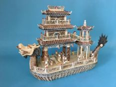 An Oriental figure group of a dragon boat