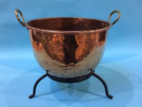 A large copper pot and stand