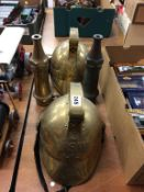 Two reproduction brass Fireman's helmets and two hose nozzles