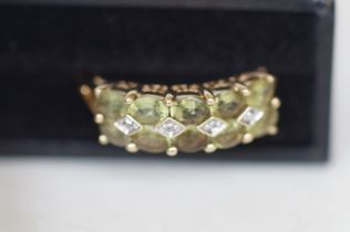9ct gold ring set with 10 light green stones and d