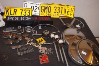 Collection of vintage car badges, steering wheel,