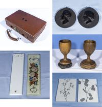 A small leather case, two wood goblets and stands, a pair of medallions, finger plates and tiles