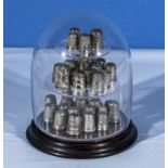 A collection of silver thimbles together with a glass dome