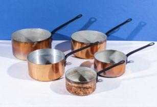 Five graduated copper saucepans