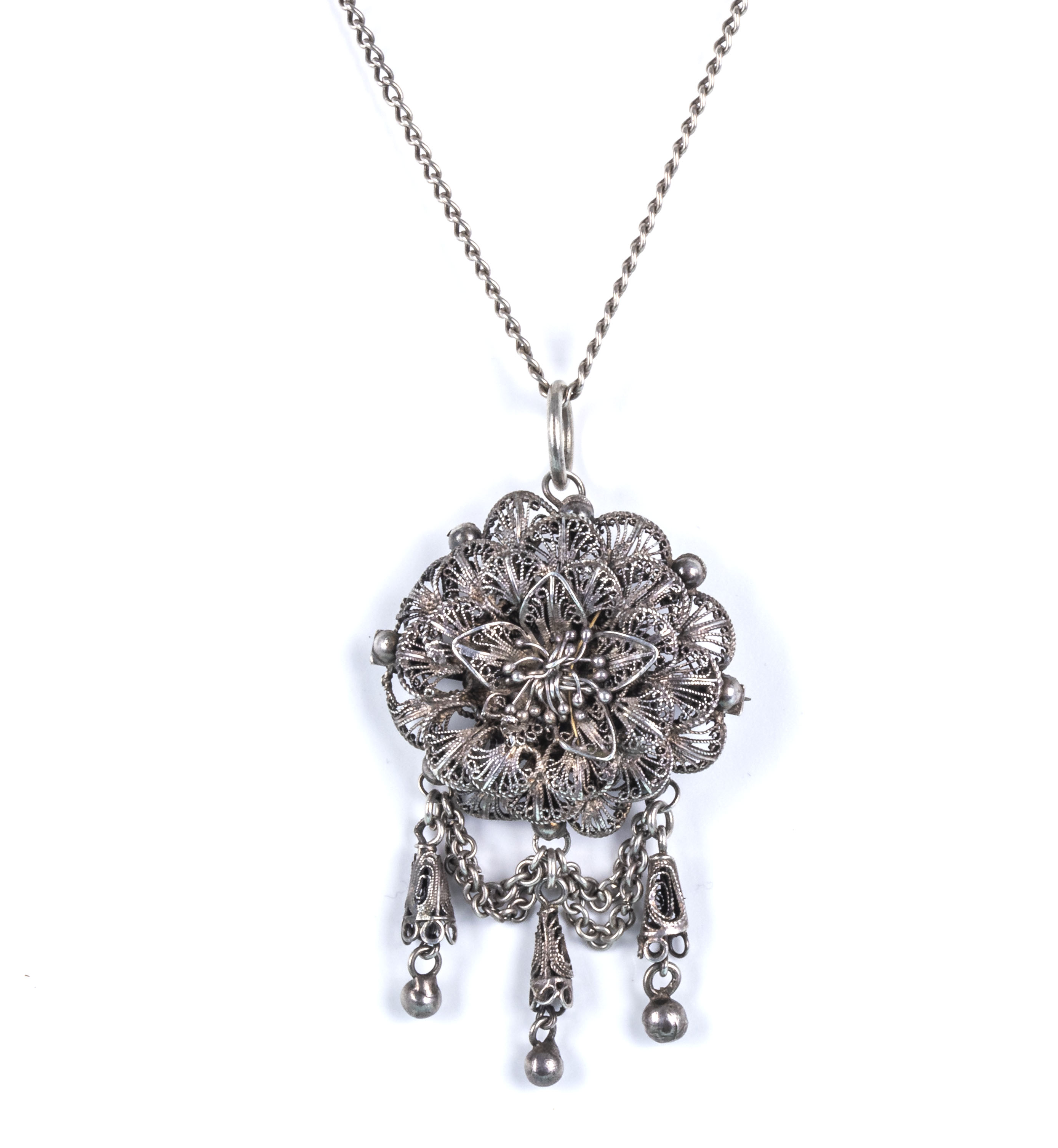 A silver brooch/pendant and chain