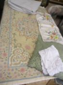 A cream crewel work rug 150 x 88cm together with mixed vintage table linen, a cushion and a large