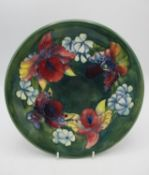 A Walter Moorcroft shallow plate in the orchid pattern on green ground, with signature, impressed