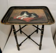 A Victorian painted tole tray with stand depicting a King Charles spaniel on a red cushion, with