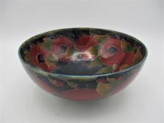 A large William Moorcroft bowl in the pomegranate pattern, raised on a small circular base, with