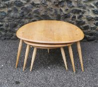 A nest of three 'pebble' Ercol tables, beech and elm, each raised on three turned splayed tapered