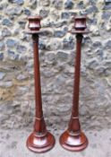 A pair of Arts and Crafts style floor standing mahogany candle holders, with tapered faceted