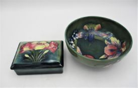 A Moorcroft pottery bowl in the Orchid pattern on a green ground, with impressed and carved marks to
