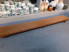 A mid 20th century low footstool with tapestry upholstery having six feet, 137 w x 20 d x 9cm h