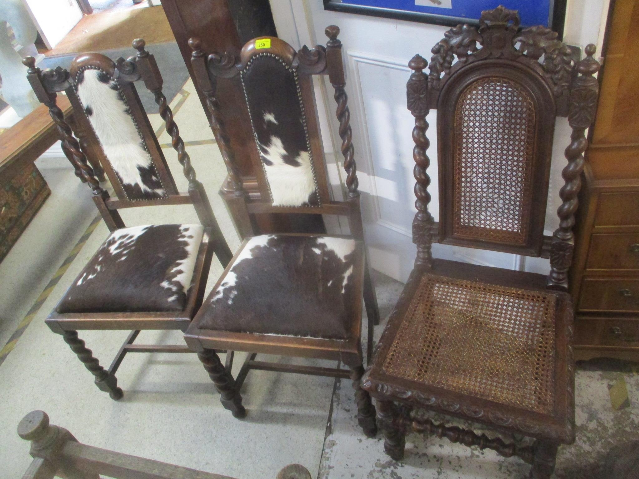 A pair of 1930's oak chairs upholstered in cow hide and an early 20th century oak framed chair