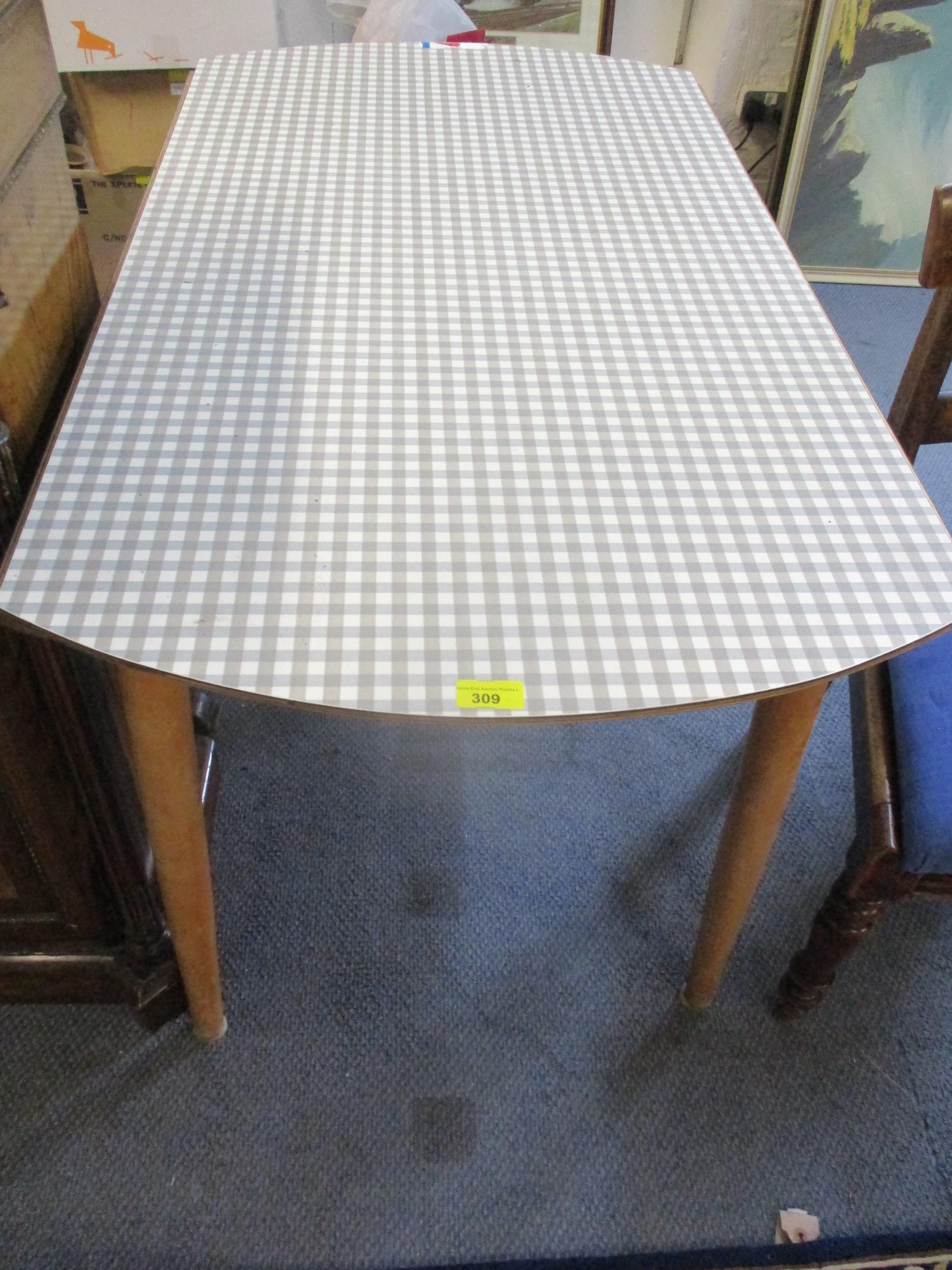A vintage folding kitchen table with chequered Formica top above light wooden legs Location: RAM