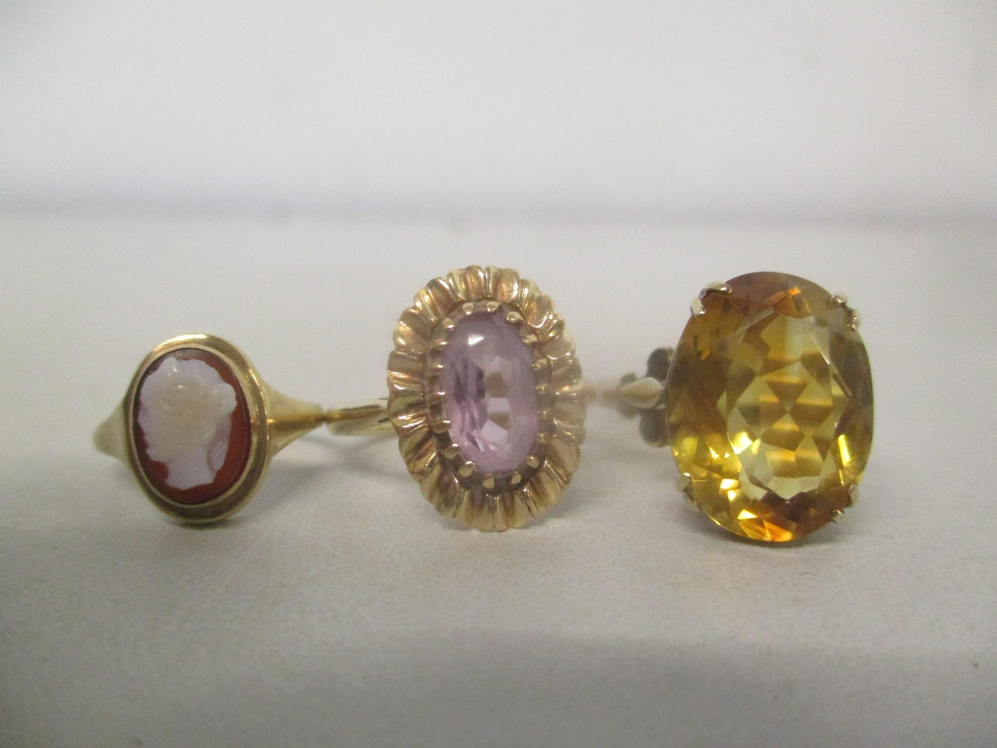 Three 9ct gold rings, one set with a citreen, one a cameo and the other an amethyst