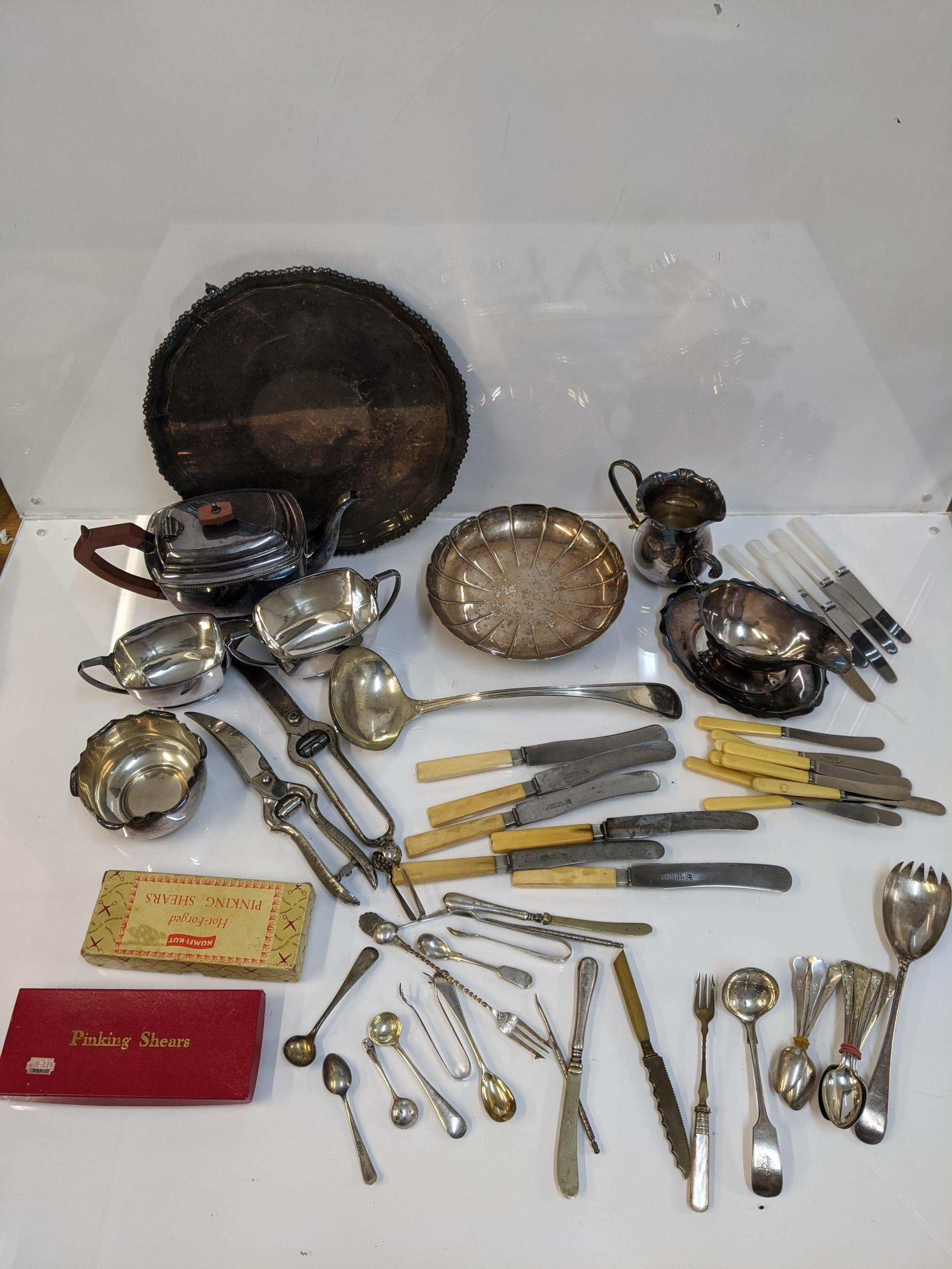 Silver plate to include a three piece tea set, sauce boats, flatware, knives and other items