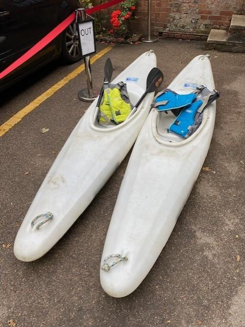 Two Kayaks together with a pair of ores and two life jackets