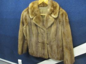 """A 1950s brown mink jacket with four buttons, approx 36"""" chest x 24"""" long, with partial belt to the"""