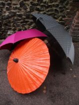 A Giorgio Armani branded umbrella and another by Charles Jourdan, together with a burnt orange