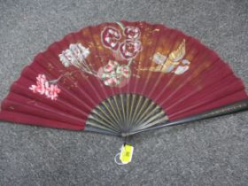 An early 20th century ebonized fan with painted images of flora and a bird against a burgundy